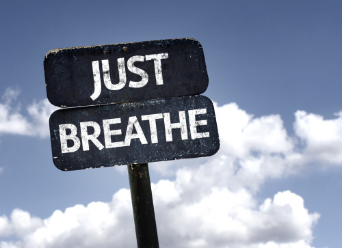 Just Breathe sign with clouds and sky background
