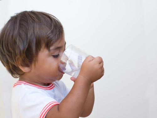 bambino beve acqua dal bicchiere